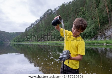 A boy in a yellow T-shirt holds a camera in his hand without a lens and pours water into it. Crazy cleaning photographic equipment in a mountain river in nature. #1457210306
