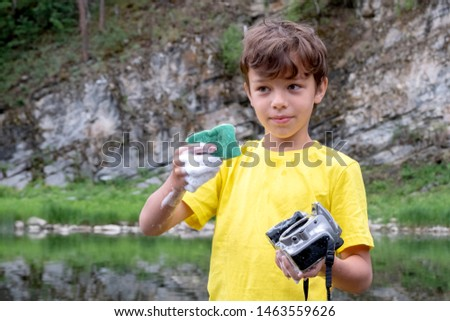 A boy in a yellow T-shirt holds a digital camera in his hand without a lens and pours water into it. Crazy mad cleaning photographic equipment in a mountain river in nature. #1463559626