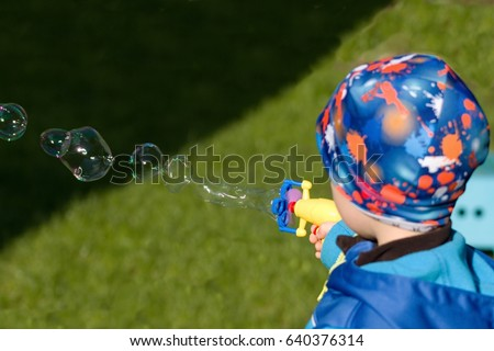 A boy in blue jacket and hat blows bubbles from toy bubble gun.Selective focus on the toy
