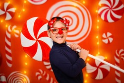 A boy in glasses with reindeer horns and a red nose holds in his hands a large toy candy while standing against a background of garlands, lollipops and sweets.
