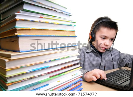 a boy in the earphones works on the computer instead of reading books