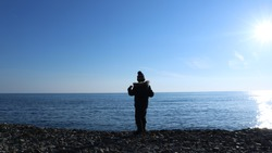 a boy in winter clothes standing facing the sea rejoices at a coastal walk, a silhouette of a young man on a rocky coast of the winter sea, one child against the background of a blue cold sea