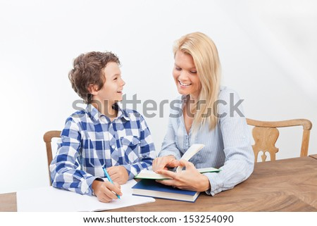 A boy is doing his homework and his mother is helping him with it. They look very happy.