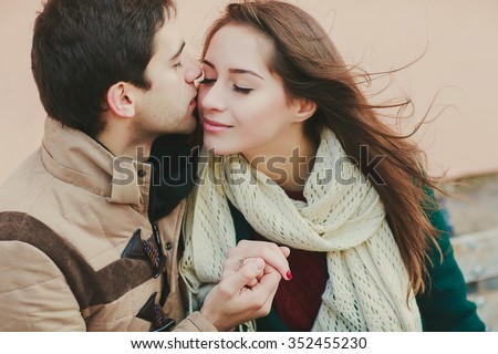 a boy is holding his girlfriend\'s hand and kissing her on a cheek, close up photo