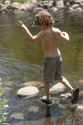 A boy is in the river, jumping on rocks. The boy does not have on a shirt. He is wearing shorts, because the summer day is warm. The kid is at camp or in the backyard, having fun and playing outside