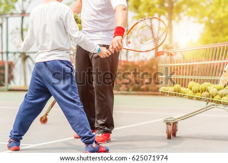 A Boy is Learning Tennis with The Trainer