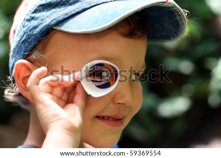 A boy is looking through a paper tube