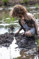 A boy is playing and digging in the wet mud outside. He is filthy, has mud from head to toe. The child is shirtless on a summer day playing in the dirt. He is having fun playing outside at camp.