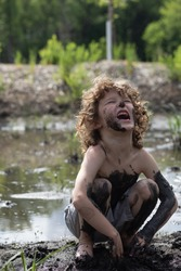 A boy is playing in a muddy swamp, and has mud all over his body. He is screaming and laughing, having fun outside in the bog. The young child is shirtless and wearing short and is really dirty.