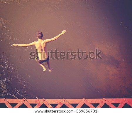 a boy jumping of an old train trestle bridge into a river done with a retro vintage instagram filter