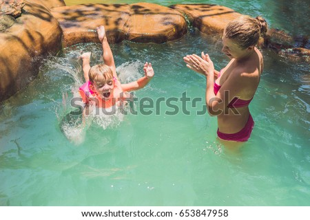 A boy jumps into the water in a pool. #653847958