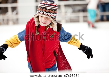 A boy just learning to ice skate.