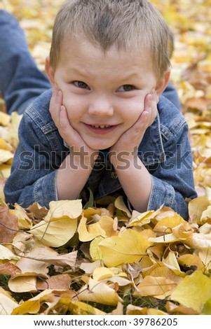 A boy laying and smiling in the fall leaves.