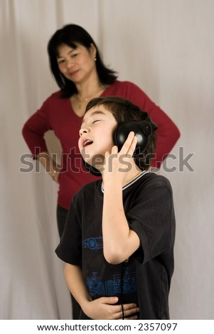 A boy listening to his music on the headphone, oblivious to his mother in the background.