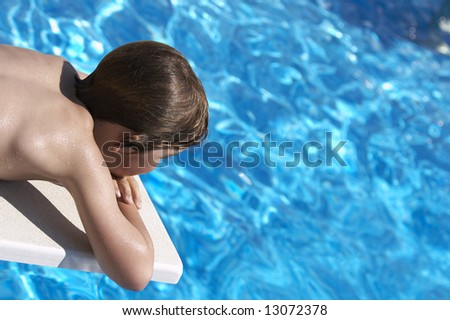 a boy looking into a pool from the diving board