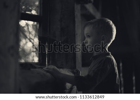 A boy looking out the window in the old house, looking for someone, a mysterious scenery, a photo for the cover of the book.