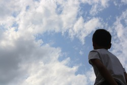 a boy looking up at the sky , a child looking up at the sky