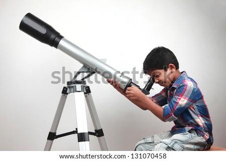 A boy looks through a telescope