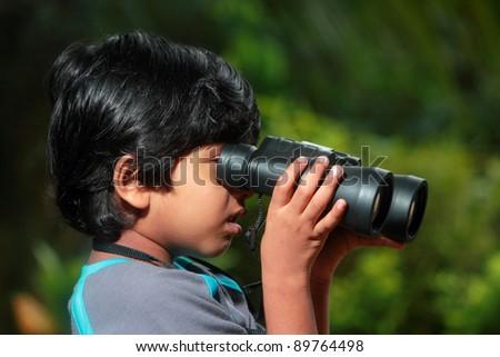 A boy looks through binoculars in outdoor