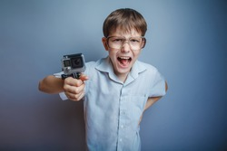 A boy of about ten European appearance in light brown shirt and glasses holding a camera and yells EKS on a gray background, videography action gopro, go pro