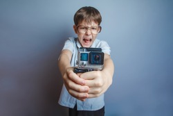 A boy of about ten European appearance in light brown shirt and glasses holding a small camera action and shouts against the gray background, video, screaming, camera gopro, go pro, action