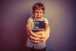 A boy of about ten European appearance in light brown shirt and glasses holding a small camera action and shouts against the GoPro gray background, video go pro, screaming, camera retro