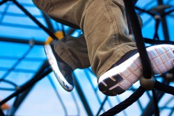 A boy on the playground climbing on a rope-ladder (web). A view of legs on the sky background. Closeup