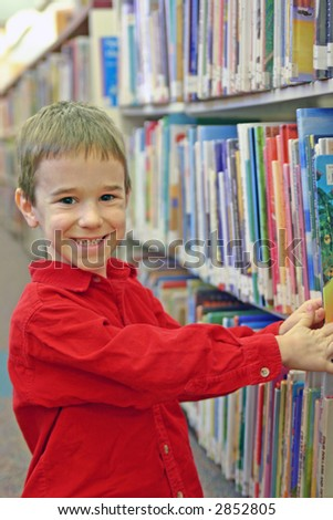A boy picking out a book at the library