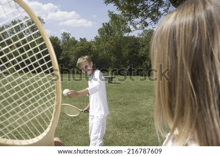 A boy playing tennis in a park.
