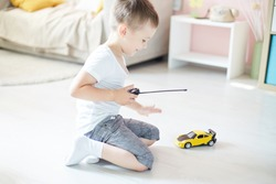 a boy playing with a car remote