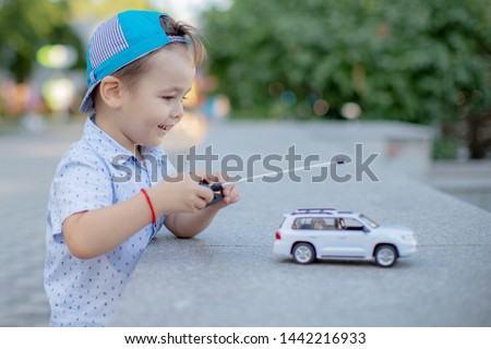 a boy playing with a car remote.a small child playing in the Park with a toy car white controls it remotely  Stock photo ©