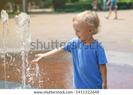 A boy playing with water in park fountain. Hot summer. Happy young boy has fun playing in water fountains