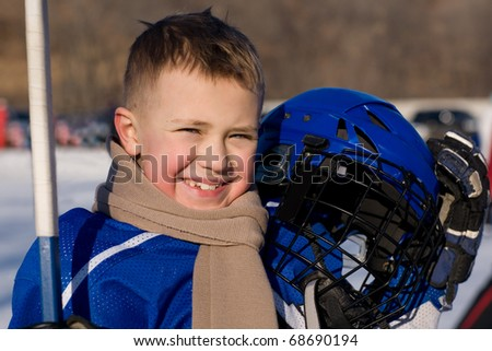 A boy plays hockey on the outdoor ice area. Boy seven years.