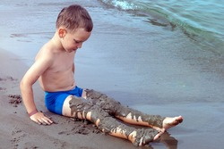 A boy plays on the seashore with sand. The child laid sand on his feet. A kid buries himself in the sand on the beach. Toned.