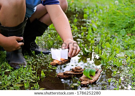 A boy plays with homemade bark boats in a stream after the rain. Children's crafts, creativity, DIY. Outdoor games. Selective focus. ストックフォト ©