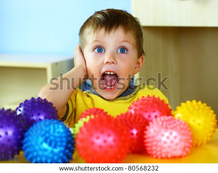 A boy plays with rubber colored balls