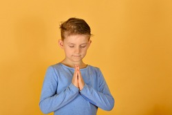 A boy prays kneeling, religious and devout children.
