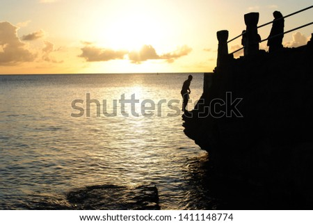 A boy prepares to do a somersault from a ledge at the Taga beach, Tinian, at sunset #1411148774