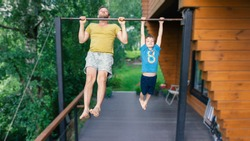 A boy pulls himself up on the bar. The son and father go in for sports. Sports family in training.The father teaches his child to achieve goals. Summer family outdoor sports workouts in the country.