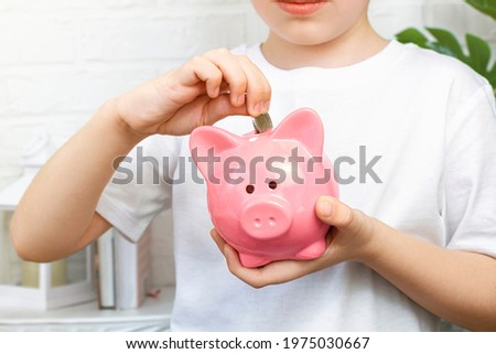 A boy puts coins in a pink piggy bank. Financial responsibility, accumulation and savings planning. The schoolboy saves money for the future, for a dream. The child manages and deposits his finances. Stock photo ©