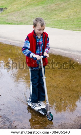 A boy rides a scooter through a puddle