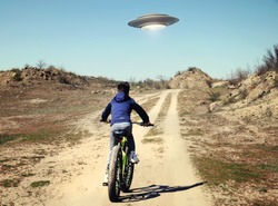 A boy riding a bicycle following a UFO. I want to believe. Photo with 3d rendering element