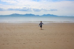 A boy running on the Newborough beach with a bucket and a stick in LLandwyn Island in Anglesey, Wales, UK. Snowdonia mountains in the background.
