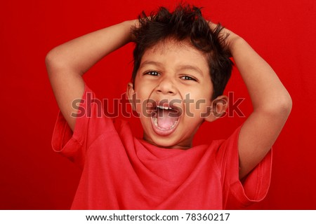 A boy screaming loud with mouth wide open