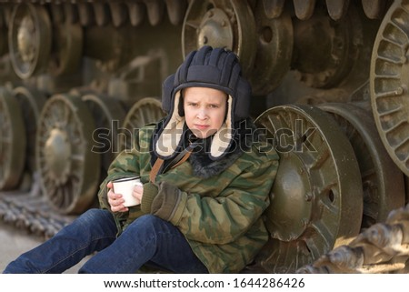 A boy sits near a tank on the street in the form of a military tanker with a mug in his hands