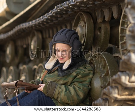 a boy sits near a tank on the street in the form of a military tanker with a tablet in his hands