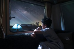 A boy sitting by the window of a van alone Look at the stars and the milky way Camping a tent in winter with family. Long exprosure with grain.