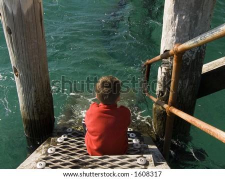 A boy sitting on a jetty