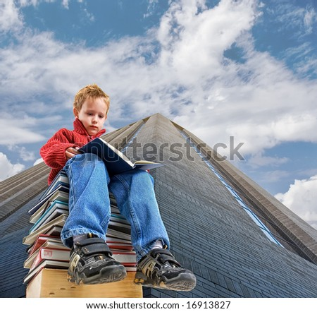 a boy sitting on a stack of books by a building