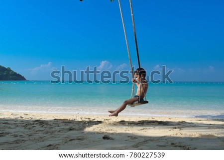 A boy sitting on swing at the beach in Thailand. #780227539